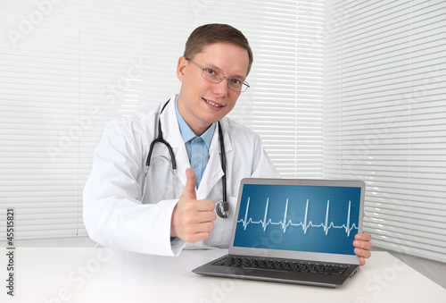 doctor with hearts beat diagram on a laptop computer