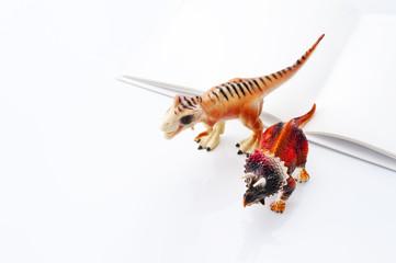 開いた本と恐竜のおもちゃ