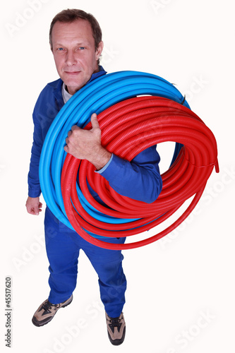 Studio shot of plumber with reels of tube