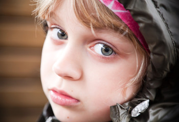 Closeup portrait of a little blond girl in a casual jacket with