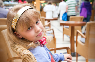 Portrait of a little blond girl in cafe