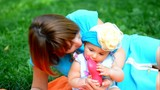Happy Mother and her baby girl play outdoor