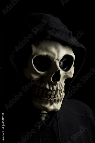 Hooded scary skeleton on black background