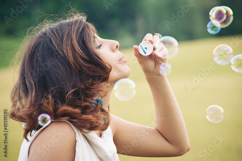 Romantic portrait of young woman with soap balloons.