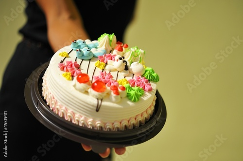 A woman holding a birthday cake