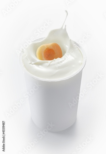 An apricot falling into a cup of yogurt