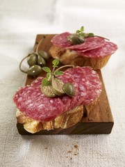 Open sandwiches with salami and capers