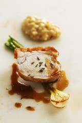 Crispy cochon de lait with caraway risotto and young onions