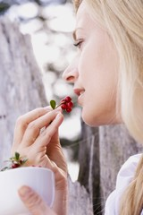 A woman eating fresh lingonberries