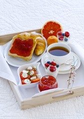 Breakfast in bed with tea, jam, yogurt, fruit and tomatoes and mozzarella