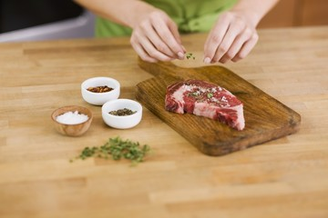 Woman Seasoning a Steak