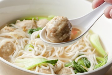 Scooping Meatball with a Spoon from a Bowl of Shanghai Noodle Meatball Soup