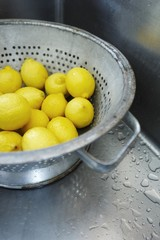 Freshly Washed Whole Lemons in a Colander in Stainless Steel Sink