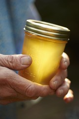 Hands Holding a Jar of Honey