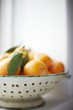 Clementines in a White Colander on a Window Sill