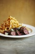 Sliced Steak with Blue Cheese and French Fries on a White Plate