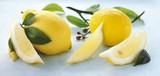 Whole lemons, lemon wedges and lemon leaves