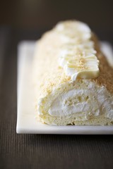 Rolled Sponge Cake with Cream Filling and Toasted Coconut on a White Platter