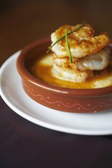 Shrimp and Grits in a Brown Dish with Chive Garnish
