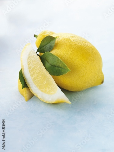 Whole lemon, lemon wedge and leaves