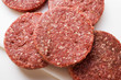 Raw burgers on chopping board
