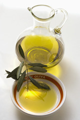 Olive oil with olive branch in bowl in front of carafe