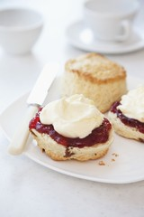 Scones with clotted cream and strawberry jam with tea cups in the background