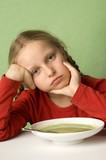 Girl sitting listlessly in front of plate of vegetable soup