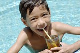 Boy drinking iced tea in pool