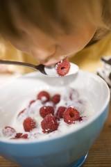 Small child eating yoghurt with fresh raspberries