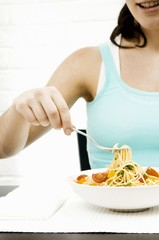 Eating spaghetti with herbs and vegetables