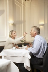Mature couple enjoying dessert in a restaurant