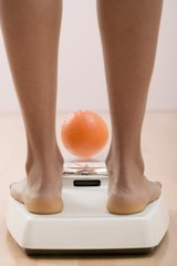 Young woman on bathroom scales with orange