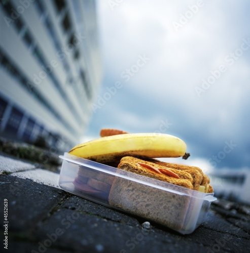 Lunch box containing cold cut sandwiches and banana