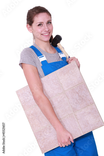 Woman with a floor tile and a mallet