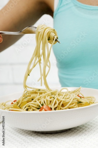 Spaghetti with herbs and vegetables wrapped round a fork