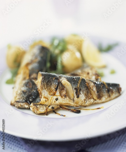 Fried sardines with onions, potatoes and rocket