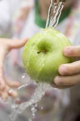 Child holding green apple under running water