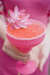 Woman holding a cocktail in a pink glass decorated with a flower