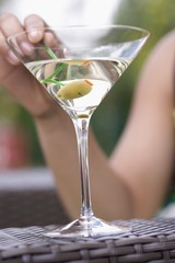 Hand holding green olive on cocktail stick in Martini glass