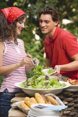Young woman serving green salad at a barbecue