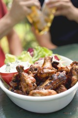 Grilled chicken wings, men with beer in background