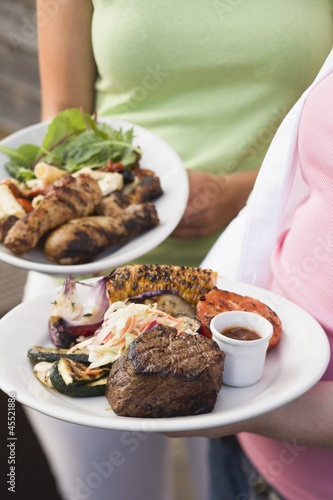 Two women holding plates of grilled food (different)