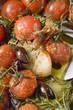 Fried cherry tomatoes with garlic and olives (close-up)