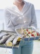 Woman holding trays of fish & kebabs ready for grilling, outdoors