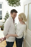 Couple under mistletoe, man holding Christmas gift