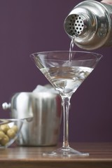 Pouring Martini out of cocktail shaker into glass