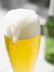Glass of lager with overflowing head of foam