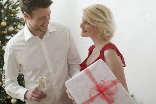 Woman holding large Christmas parcel, man holding glass of wine