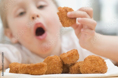 Little girl eating chicken nuggets